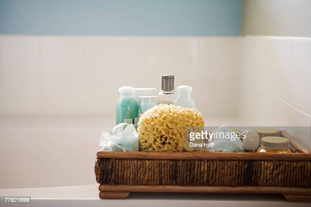 A wooden bath caddy filled with natural beauty tools