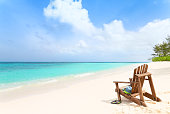 Wooden beach chair with hat, sunglasses and slippers at tropical beach, summer holiday concept
