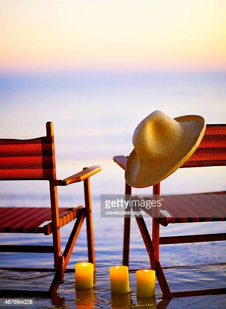 Wooden beach chairs on beach at sunset or sunrise,