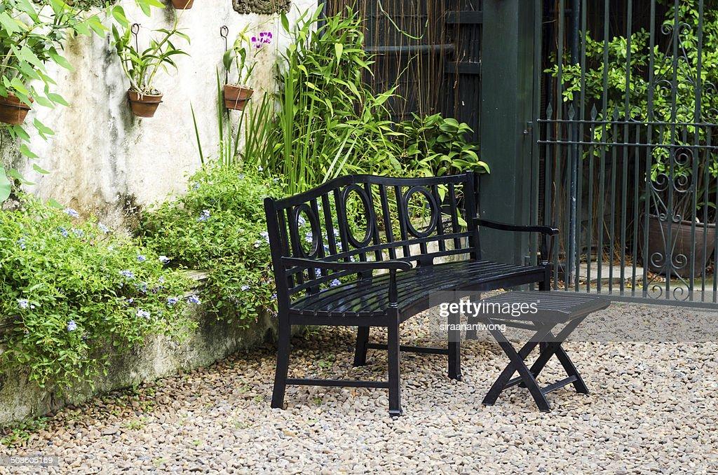 Banco de madeira e mesa em um Jardim de Pedra : Foto de stock