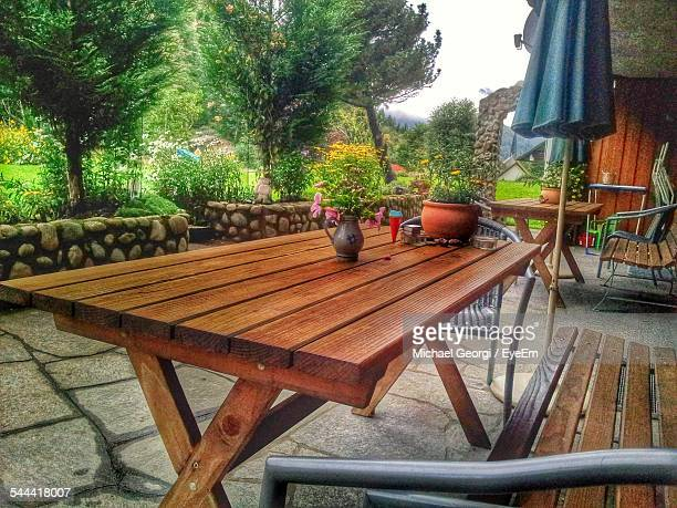 Wooden Bench And Tables Arranged In Yard