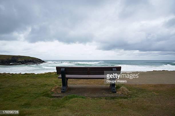 Wooden bench facing sea on UK coastline.