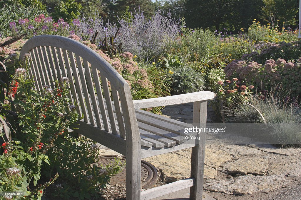 Wooden Bench In Formal Garden Flower Bed With Stone Patio : Stock Photo