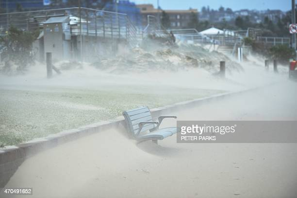 A wooden bench is covered in sand whipped up by strong winds at Bondi Beach in Sydney on April 21 2015 Sydney and surrounding areas were lashed by...