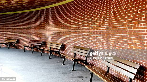 Wooden Benches In Row Against Brick Wall