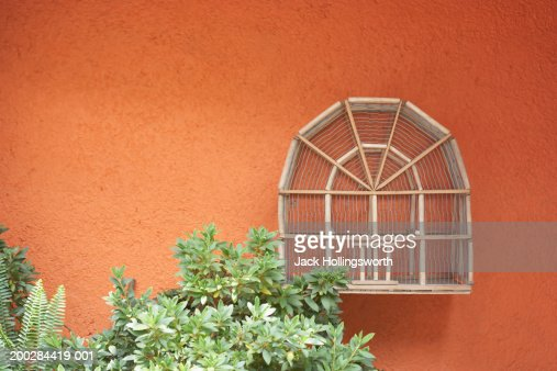 Wooden bird cage hung on a stucco wall