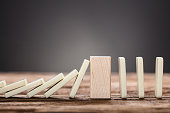 Closeup of wooden block amidst falling and upright domino pieces on table against gray background