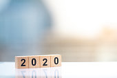 Wooden block number of year 2020 on cityscape background with copy space.