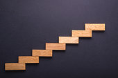 Top view wooden block set up for staircase on black stone board. Business concept for growth success process.