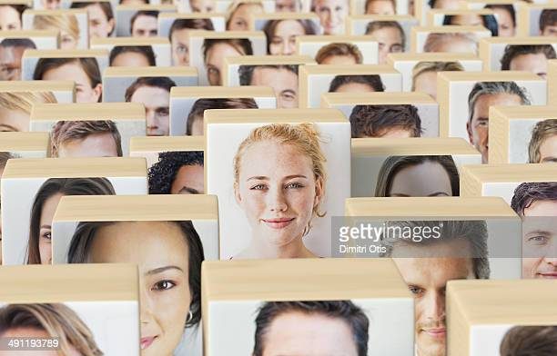 Wooden blocks with portraits, one standing out