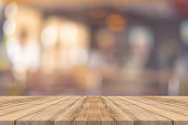 Wooden board empty table in front of blurred background. Perspective brown wood over blur in coffee shop - can be used for display or montage your products.Mock up your products.Vintage filter.