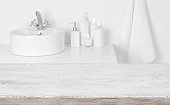 Wooden board in front of blurred domestic bathroom washbowl background
