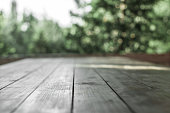 Wooden board  in front of the blurred nature background.