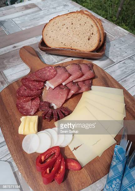 A wooden board of cured ham and salami mountain cheese sliced radish red pepper butter and bread await a visitor at a hut in the Raetikon mountain...