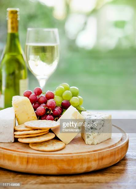 Wooden board with cheese, grapes and wine in the background