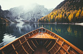 Scenic view of traditional wooden rowing boat gliding on famous Lago di Braies in the Italian Dolomites on a beautiful sunny day in fall with retro vintage filter effect, South Tyrol, Italy