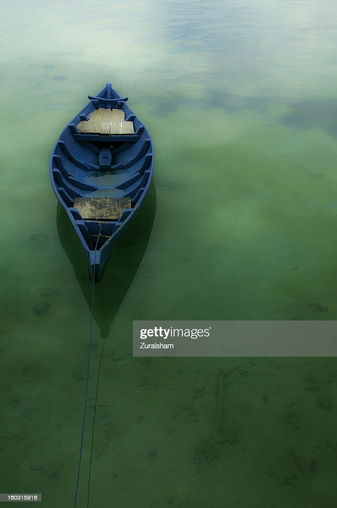 Wooden Boat on crystal clear water : Stock Photo
