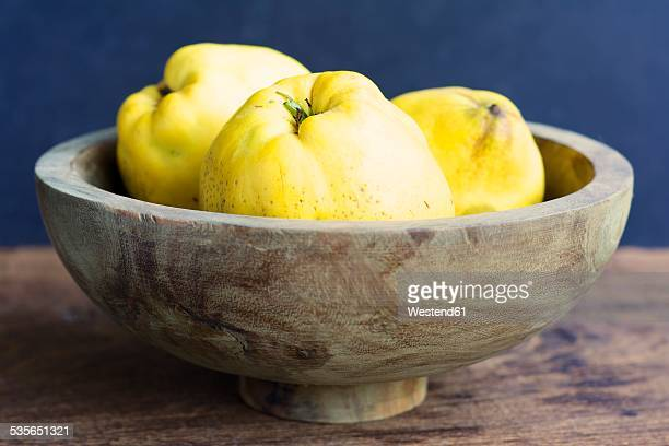 Wooden bowl of quinces, Cydonia oblonga
