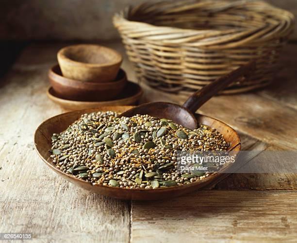 Wooden bowl with pumpkin seeds, golden linseeds on hemp seeds on wooden table