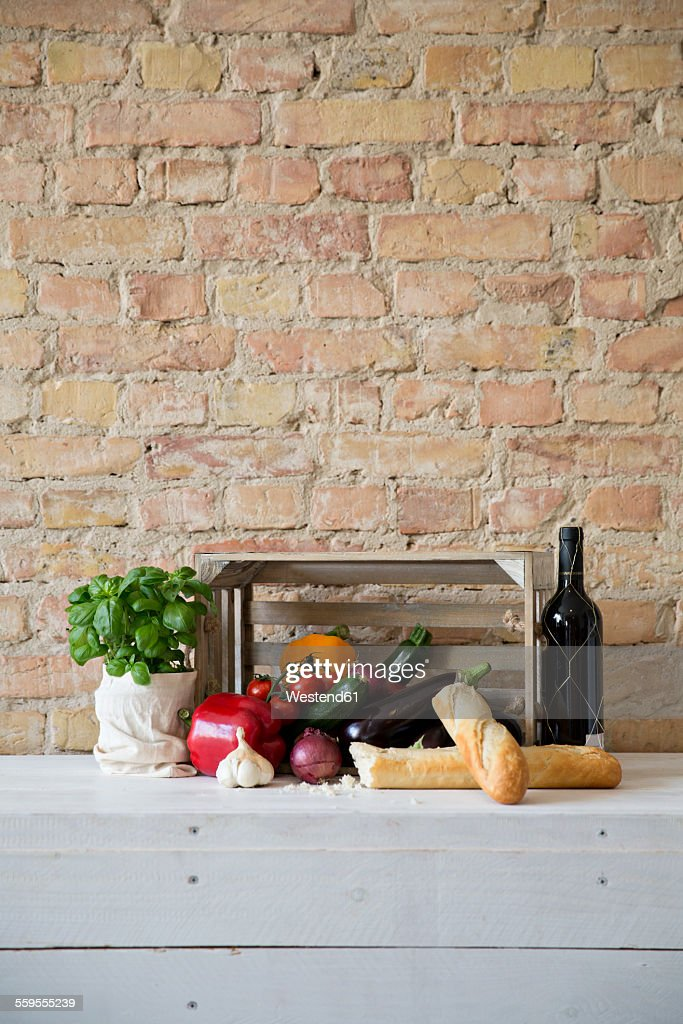 Wooden box with vegetables, baguette, basil and wine bottle