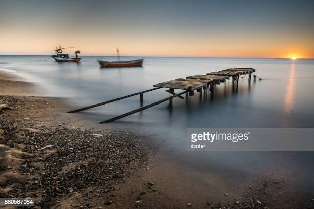 Wooden bridge laying to the sea at sunset
