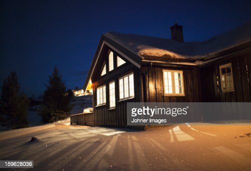 Wooden cabin in snow at night