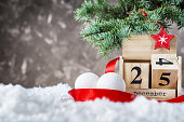 Wooden calendar flipped from 24 to 25 December. Wooden calendar with holiday balls and red ribbon on snow on gray background. Christmas date on calendar. Empty copy space for inscription. Xmas concept