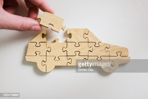 Wooden car jigsaw puzzle, final piece being placed