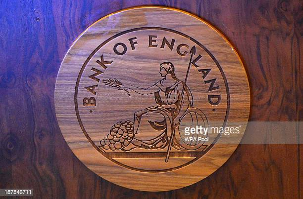 A wooden carving of the Bank of England logo is seen on a desk during the bank's quarterly inflation report news conference at the Bank of England on...
