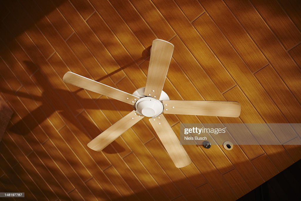Wooden ceiling fan casting shadows : Stock Photo