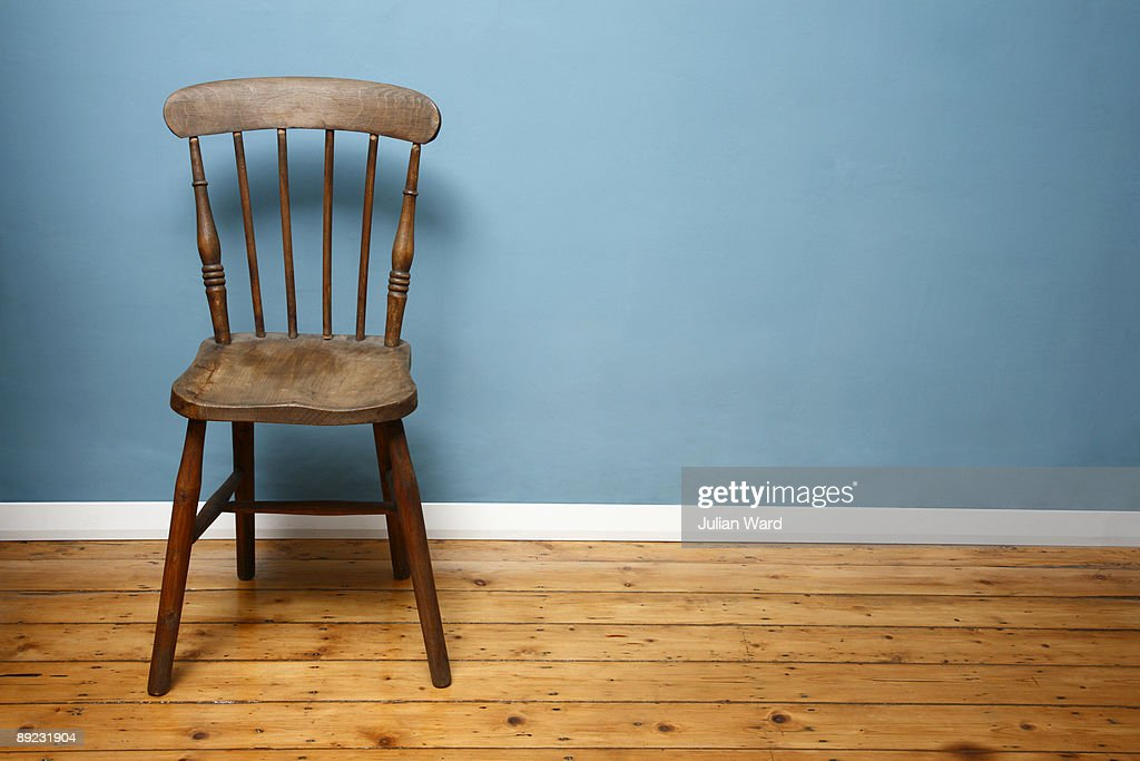 Wooden chair against a blue wall in an empty room : Stock Photo