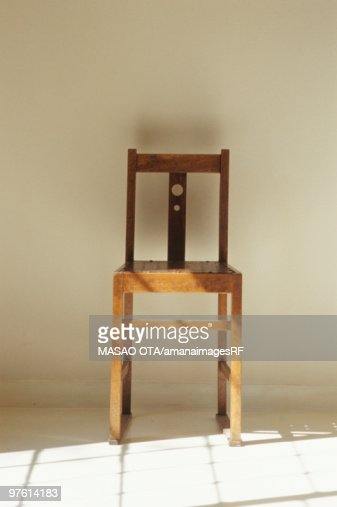 Wooden chair next to shadow cast by window stock photo for Chair next to window