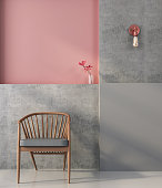 Wooden chair on the background of a wall with geometric shapes in pink and gray colors