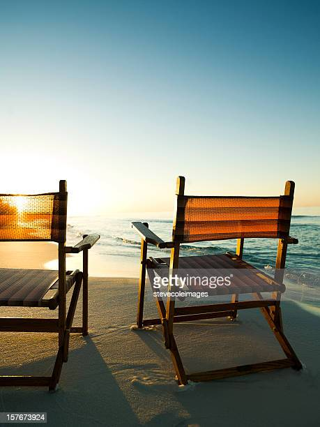 Wooden Chairs on Beach at Sunrise