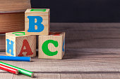 Children's wooden blocks with letters and colored pencils lying on a wooden table. Closeup.