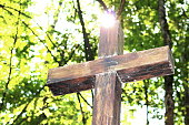 Wooden Christian religious cross on the background of green trees and rays of sunlight at dawn