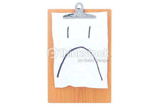 wooden clipboard with white rough paper and a sad face stock photo