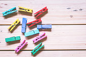 Wooden colored clothespins on wooden background