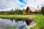Large wood and stone log home surrounded by a cloudy sky and a lake.