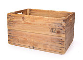 Old wooden box isolated on white background showing signs of extensive use like stains and scratches. These crate's where used for potato storage.