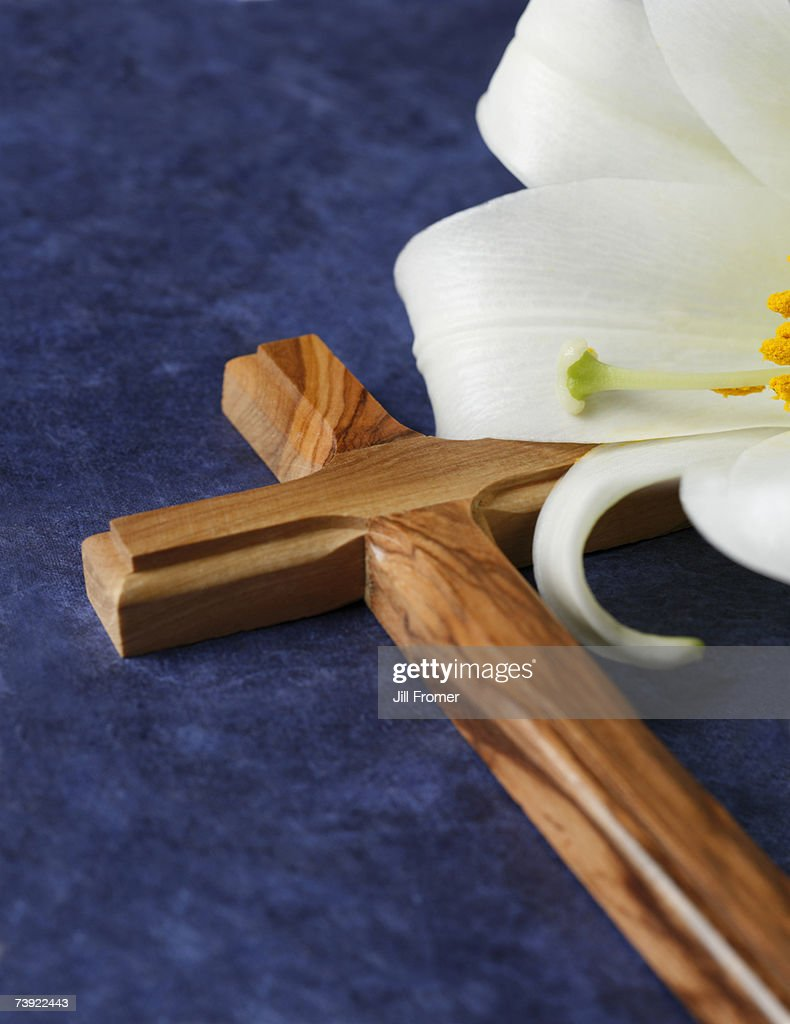 A wooden cross and an Easter lily on a blue background : Stock Photo