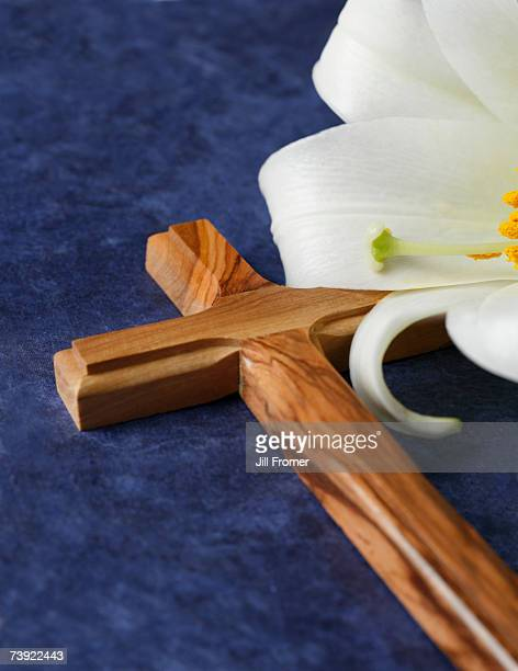 A wooden cross and an Easter lily on a blue background
