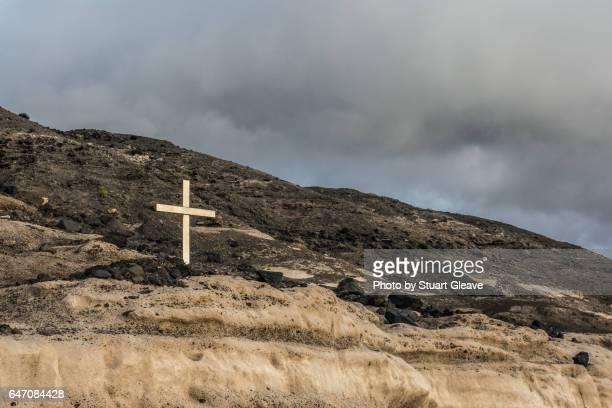 Wooden cross on rocky coastline