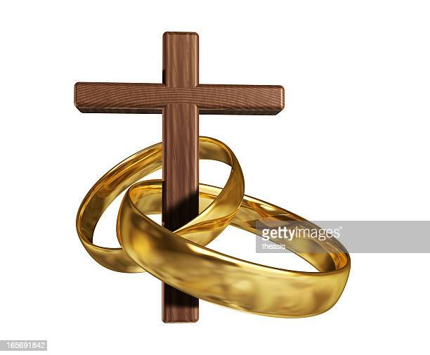 Wooden cross threaded through two gold wedding rings