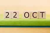 Wooden cube shape calendar for OCT 22 on green book, table.