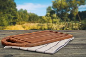 Wooden Cutting Board Close-up On The Picnic Table And Summer Landscape In Blurred Perspective