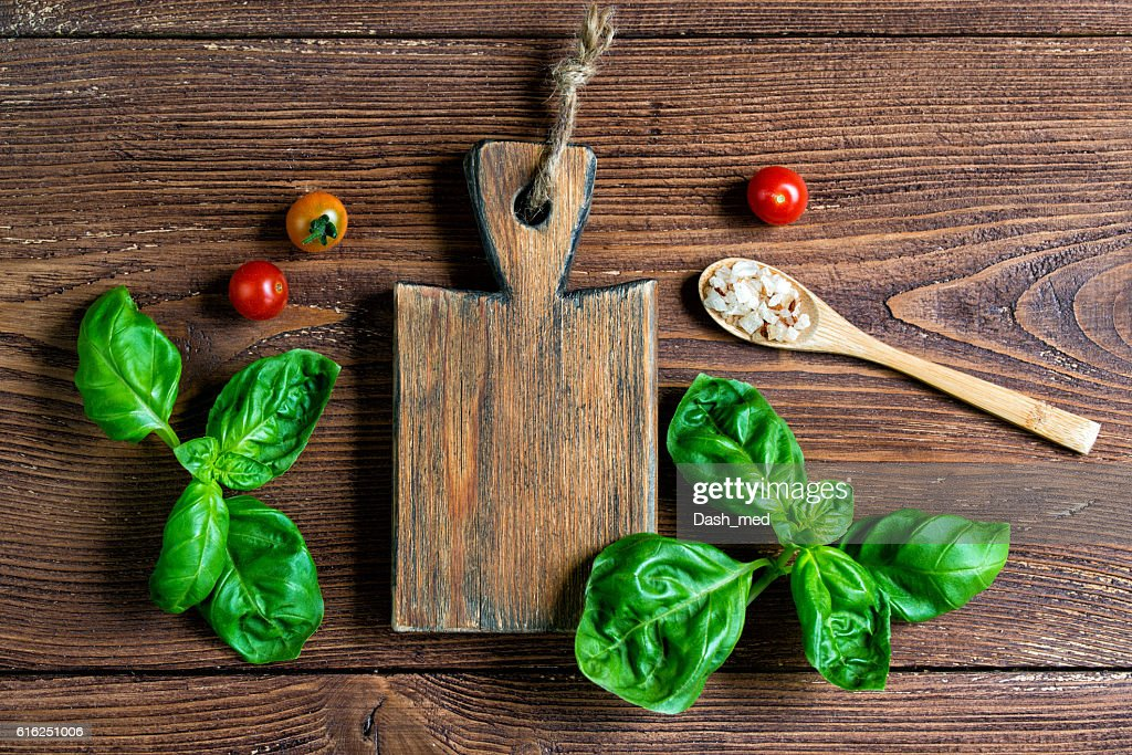 Wooden cutting board, salt, fresh basil leaves and cherry tomatoes : Foto de stock