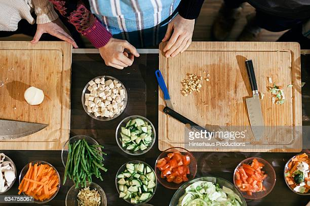 Wooden cutting board with bowls and vegetables
