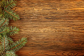 Wooden dark background for Your Christmas titles. Branches of blue spruce. The view from the top.