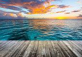 wooden deck at caribbean sea at sunset